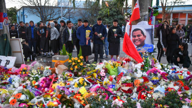Flowers and mourners pay tribute to the slain schoolboy.