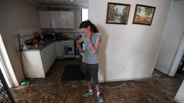 Sue Pollard becomes emotional as she walks around her flood-affected house in the suburb of Hermit Park in Townsville