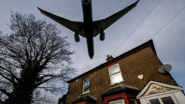 A plane comes in to land at Heathrow airport over nearby houses in London.