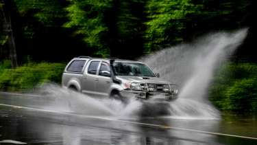 Cars drive through water over Alexandra Avenue.