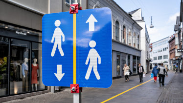 A yellow stripe painted to help shoppers to maintain social distancing in the middle of the pedestrian shopping street in Aalborg, Denmark.