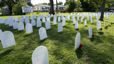 White plastic tombstone-shaped pieces are lined up as a temporary memorial to some of Miami's victims of the coronavirus at Simonhoff Floral Park.