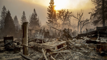A vintage car rests among debris as the Camp Fire tears through Paradise, California.