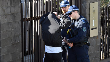 Police speak to a man outside John Ibrahim's home.