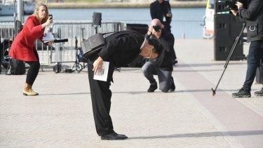 A man bows towards the screen at the end of Bob Hawke's memorial service.