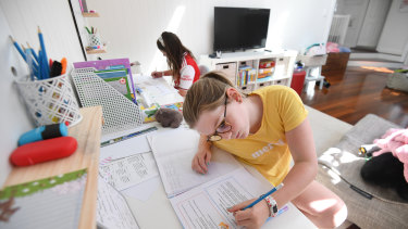 Grace Merriman (front), 8, and her sister Audrey, 9, are seen learning from home on the first day of term 2 in Brisbane.