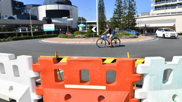 A cyclist is seen riding past a barrier across the Queensland and New South Wales border in Coolangatta during the lockdown.