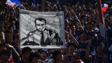 "F. Marinos fans hold up a banner saluting Postecoglou as ""brave and challenging""."