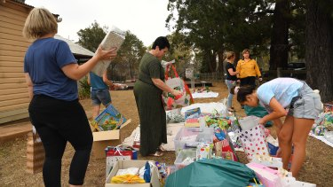 Community members sort out donated Christmas presents into categories in Balmoral, which was severely impacted by fires.