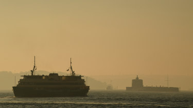 A commuter ferry moves through the thick smoke blanketing Sydney Harbour on Friday morning.