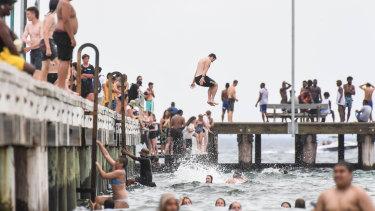 Thrill seekers take a plunge off Frankston pier on Monday.