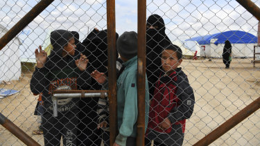 Foreign IS wives and children at the fence line of the foreign section of Al Hawl camp in Syria.