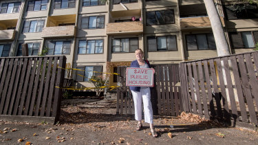 Eileen Artmann in front of the public housing estate where she has lived for 41 years. She does not want to go, and says the deal the government has cut with a developer is not in residents' best interests.