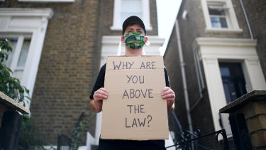 A protester holds up a placard which reads 'Why are you above the law?' outside the home of Dominic Cummings.