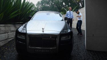 Michael Pallier talks to a Chinese client next to his Rolls-Royce.