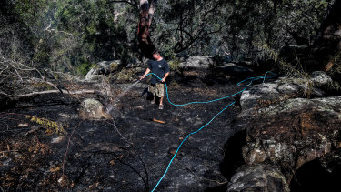 Justin Frith hoses down an area behind his home in Menai in Sydney.
