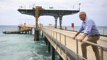 Prime Minister Scott Morrison poses for photographs on the Christmas Island jetty.