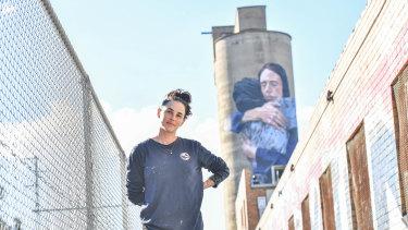 Artist Loretta Lizzo in front of her Brunswick silo mural of Jacinda Ardern.