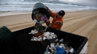 Clean up contractor Derrick Kennedy clearing debris from the beach at Hawks Nest near Port Stephens.