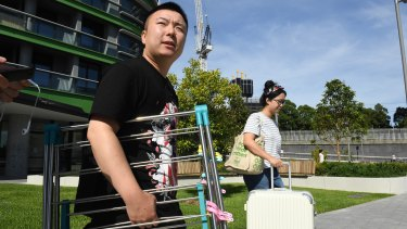 Qi, left, leaves Opal Tower on Friday, as he weighs up whether to return permanently.