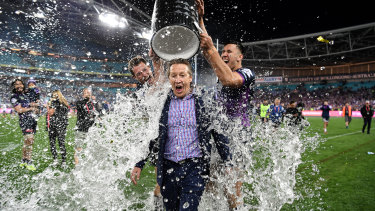 Craig Bellamy gets doused after winning the 2017 grand final.