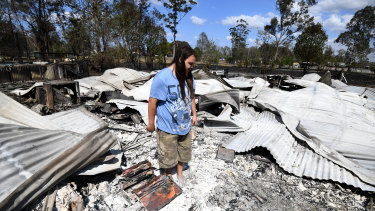 Liam McKenzie inspects the remains of his house, which was destroyed by bushfires.