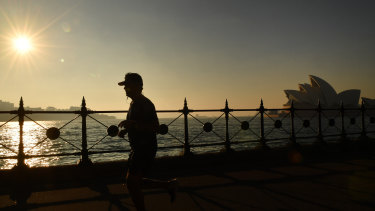 A jogger runs along Sydney Harbour as thick smoke blankets the greater Sydney Basin.