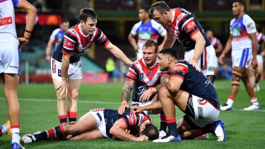 Roosters players show their concern for Boyd Cordner after the skipper went down against the Knights.