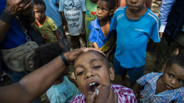 A child in Papua New Guinea receives a polio vaccine. The coronavirus outbreak threatens to reverse decades of progress in alleviating poverty.