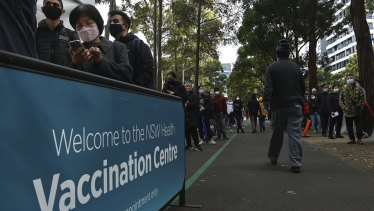 People queue for COVID-19 vaccinations at the NSW Health Vaccination Centre at Olympic Park.
