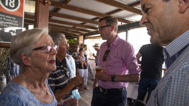 NSW Treasurer Dominic Perrottet, background, meets locals at the Nevertire Pub on a road trip from Dubbo to Bourke.