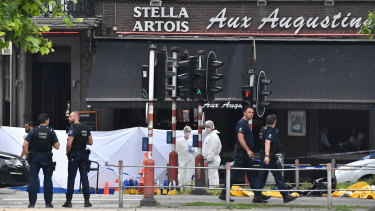 Police investigating the scene after a gunman killed three people, including two police officers.