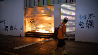 A man walks in front of a branch of Bank of China set ablaze during a protest against a government ban on face masks.