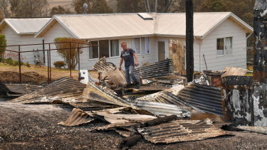 Giovanni Kilman outside his home after fires ravaged his property.