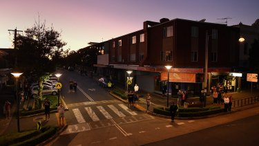 People listen to bugler Sarah Brown as she plays The Last Post from the balcony of The Royal Hotel on Norton Street in Leichhardt at dawn on ANZAC Day. Leichhardt.