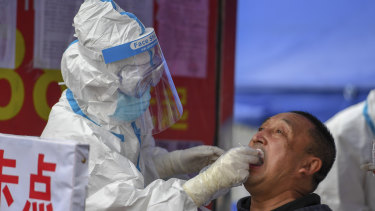 A medical worker collects a sample for COVID-19 testing at the Tongji community in Shulan in China's Jilin Province.