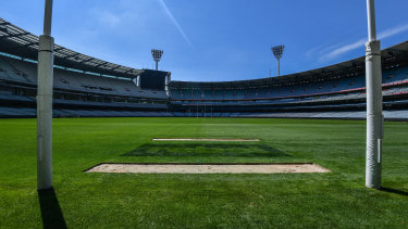 Two strips of grass from the MCG goal square are dug up and will be sent to the Gabba for the grand final.
