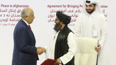 US peace envoy Zalmay Khalilzad, left, and Mullah Abdul Ghani Baradar, the Taliban group's top political leader, shake hands after signing a peace agreement in Doha, Qatar, in February.