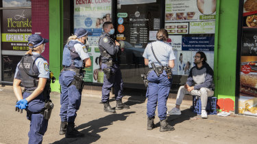 Out in force: Police in western Sydney speaking to a man not wearing a mask.