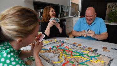 Andrew Baume and his wife Robyn (centre) and family friend Elizabeth Hunter (left) play board games in Sydney rather than holiday along the South Coast, as per their original plans.