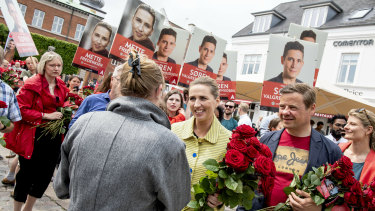 Mette Frederiksen, centre, gives away roses to voters in the last minutes of her campaign in her hometown of Aalborg, along with its mayor, Thomas Kastrup-Larsen, right.