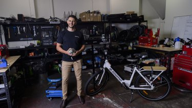 Zoomo chief executive and co-founder Mina Nada holds an engine from one of the company's bikes at its Surry Hills, Sydney, store.