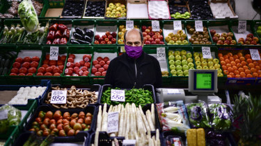 Is four days enough? A man minds his fresh food market stall in Pamplona, northern Spain.