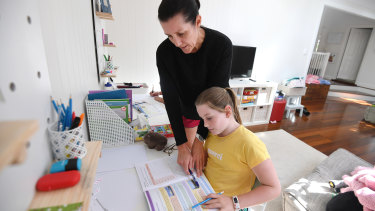 Michelle Merriman helps her daughter Grace, 8, with schoolwork as she learns from home in Brisbane.