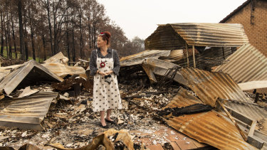 Donna Combe, one of Conjola's residents, stands amid the ruins of her home.