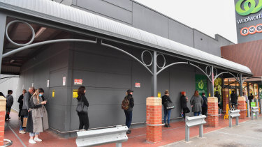 People queue to shop at a Woolworths in Victoria at the height of demand.