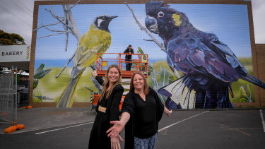 Wonthaggi Business and Tourism Association president Amy Easton (left) and bakery co-owner Dee Connell in front of Jimmy Dvate and his artwork in Wonthaggi.