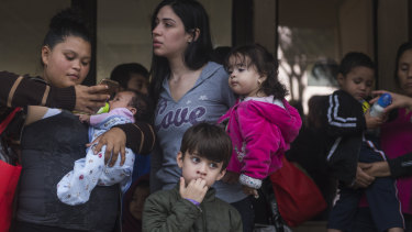 Central American migrant families wait to be taken to the McAllen bus station from the Catholic Charities Humanitarian Respite Centre, in McAllen, Texas.