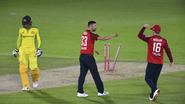 England's Mark Wood, center, celebrates with captain Eoin Morgan, right, the dismissal of Australia's Alex Carey.
