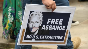 A supporter of Julian Assange and WikiLeaks holds a placard during a snap rally in Sydney on Friday.